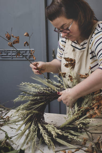 Woman making a winter wreath, adding dried grasses and seedheads and twigs with brown leaves. — Stock Photo
