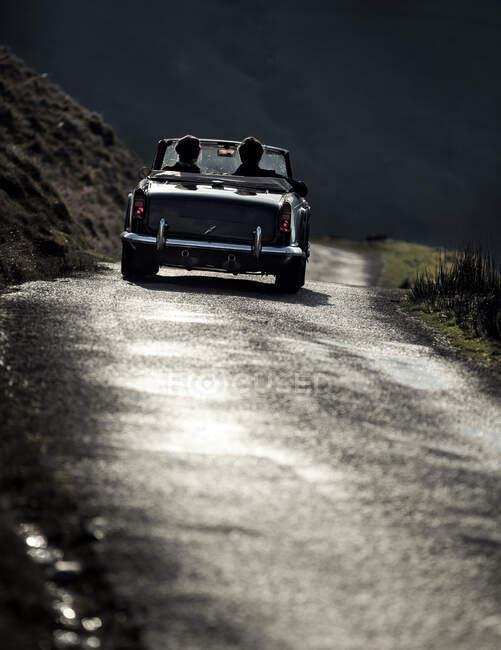 Rückansicht von zwei Personen in einem Cabrio, das auf einer Landstraße fährt. — Stockfoto