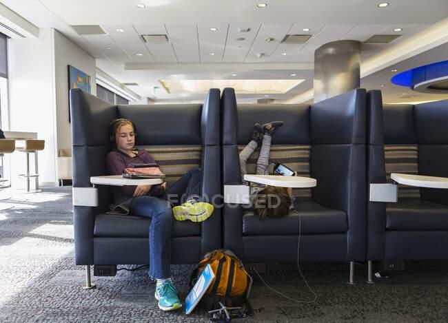 Двоє дітей дивляться свої цифрові планшети, чекаючи на літак у залі вильоту в аеропорту. — стокове фото