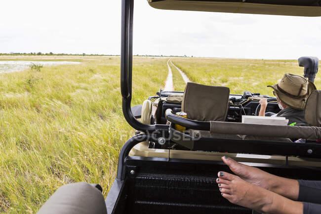 Обрезанный снимок человеческих ног в сафари-машине, Ботсвана — стоковое фото