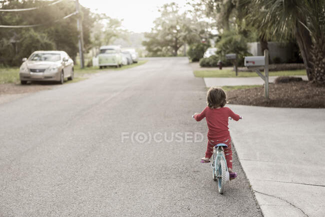 A five year old boy in a red shirt riding his bike on a quiet residential street. — Stock Photo