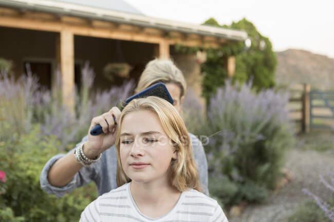 Femme brossant les cheveux blonds d'une adolescente dans un jardin. — Photo de stock