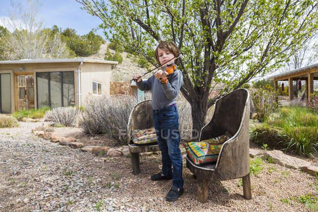 Garçon de 6 ans jouant du violon en dehors de sa maison — Photo de stock
