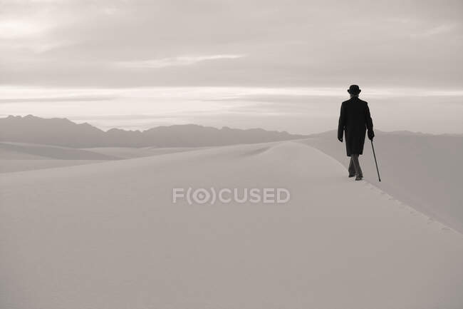 Man in a black coat and suit, a bowler hat and umbrella, in a white desert wilderness of white sand. — Stock Photo