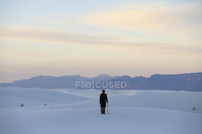 Человек в черном пальто и костюме, шляпа-котелок и зонтик, в белой пустыне с белым песком. — стоковое фото