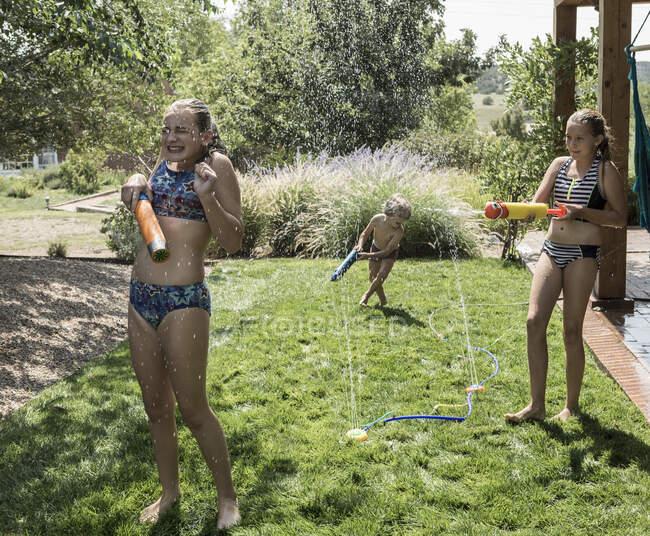 Bambini che si spruzzano a vicenda con tubi dell'acqua — Foto stock