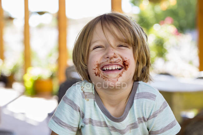Portrait of smiling 4 year old boy with chocolate on his face playing and laughing — Stock Photo