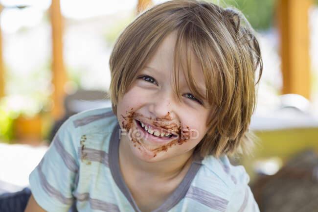 Портрет улыбающегося 4-летнего мальчика с шоколадом на лице, играющего и смеющегося — стоковое фото
