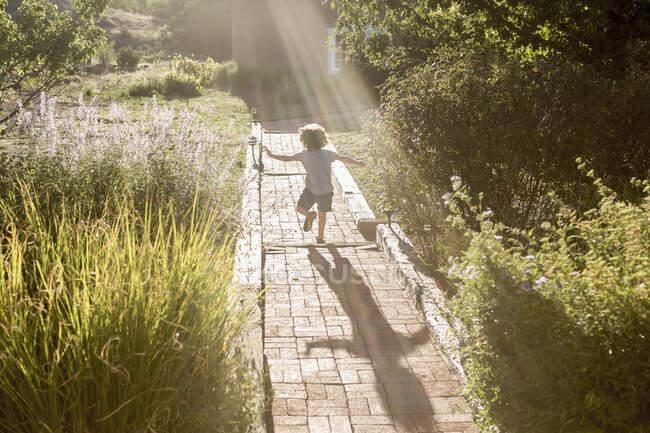 4-летний мальчик бегает по кирпичной дорожке — стоковое фото