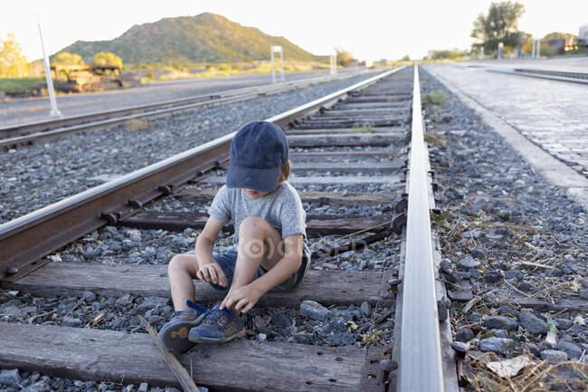 4 anni ragazzo seduto su binari ferroviari, Lamy, NM — Foto stock