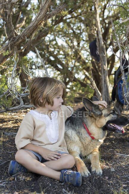 4 - річний хлопчик, який подорожує зі своїм німецьким собакою - пастухом. — стокове фото
