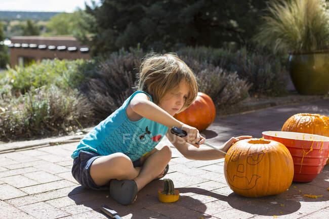 4 anos de idade menino esculpindo uma abóbora — Fotografia de Stock