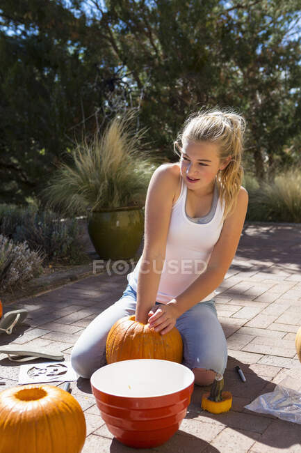 11 year old girl digging out a pumpkin — Stock Photo