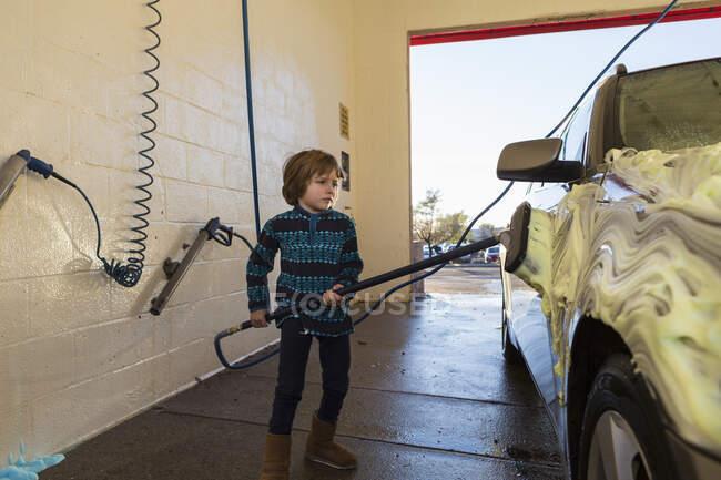 4 year old boy washing a car in car wash — Stock Photo