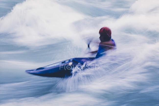 Lunga esposizione di kayaker kayaker uomo whitewater pagaiare e surf grandi rapide su un fiume che scorre veloce. — Foto stock