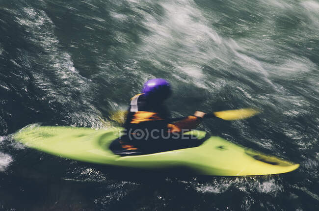 Whitewater kayaker remare grandi rapide fluviali su un fiume che scorre veloce — Foto stock