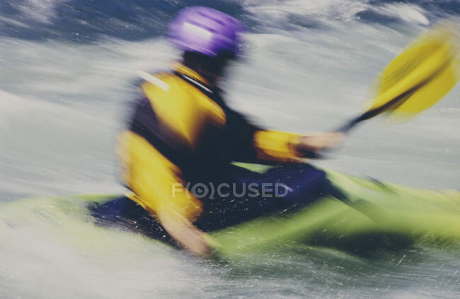 Lunga esposizione di femmina kayaker whitewater pagaiare rapide e navigare su un fiume che scorre veloce. — Foto stock
