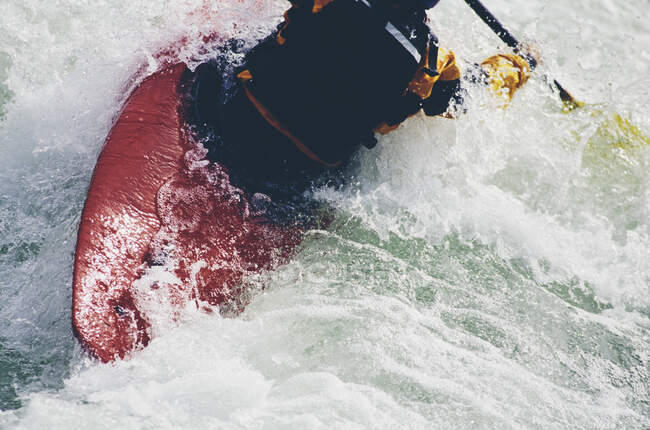 Kayaker kayaker femminile che rema rapide e naviga su un fiume che scorre veloce. — Foto stock