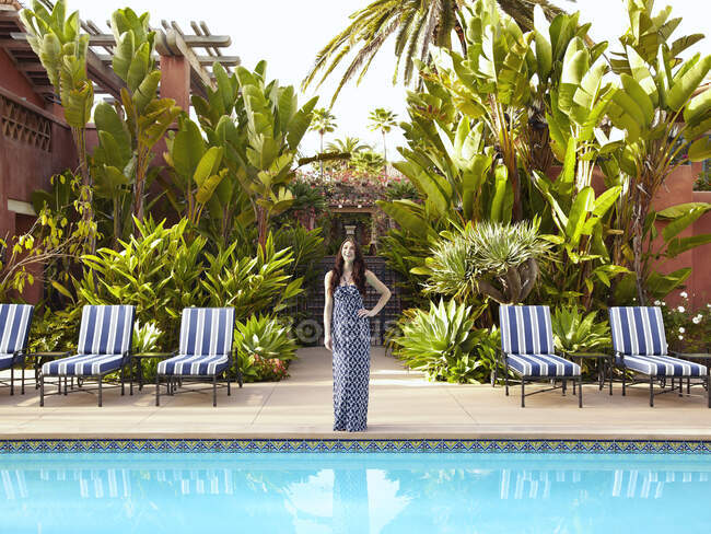 Bella giovane donna in piedi vicino alla piscina — Foto stock