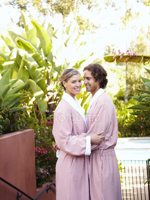 Белая пара в халатах, обнимающая — стоковое фото