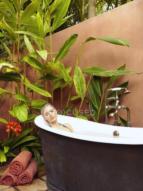 Красивая молодая женщина, купающаяся в старомодной ванне — стоковое фото