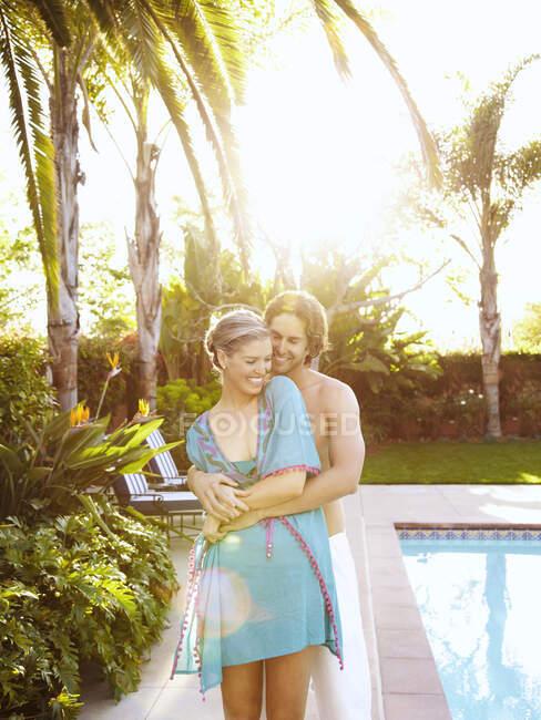 Coppia caucasica che si abbraccia a bordo piscina — Foto stock