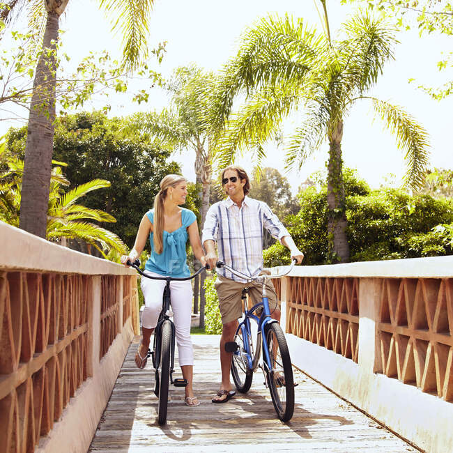 Кавказька пара їздить на велосипедах через міст. — стокове фото