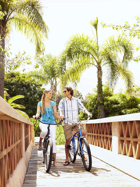 Caucasian couple riding bikes over bridge — Stock Photo