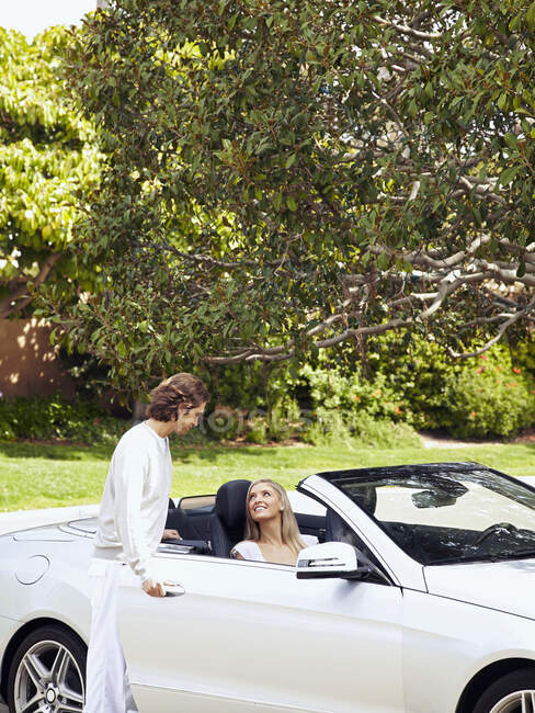 Caucasian man helping wife into convertible car — Stock Photo