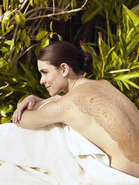 Beautiful young woman having mud spa treatment — Stock Photo