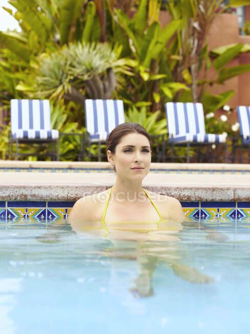 Bella giovane donna rilassante in piscina — Foto stock