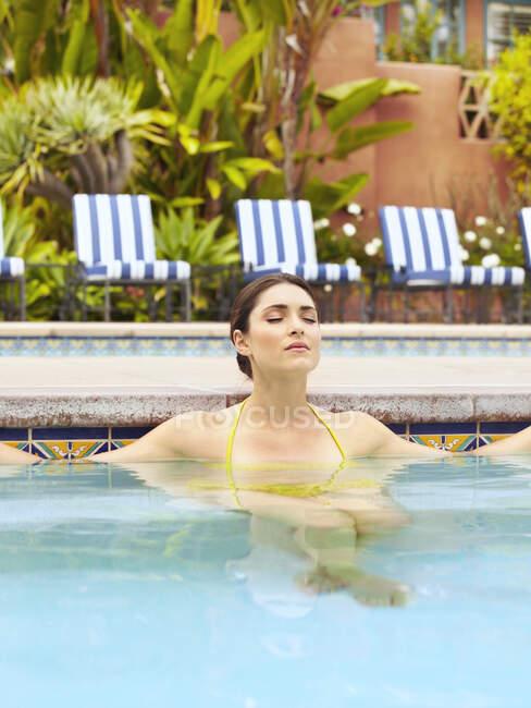 Beautiful young woman relaxing in swimming pool — Stock Photo