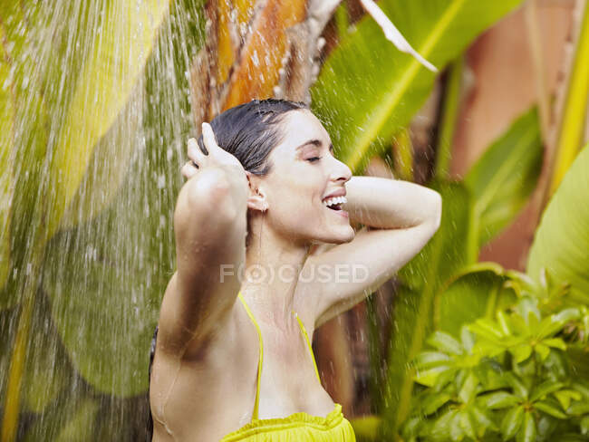 Beautiful young woman in bikini showering outdoors — Stock Photo