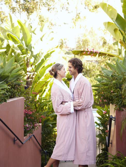 Kaukasisches Paar in Roben umarmt — Stockfoto