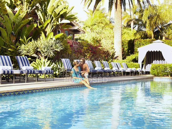 Coppia caucasica seduta a bordo piscina — Foto stock