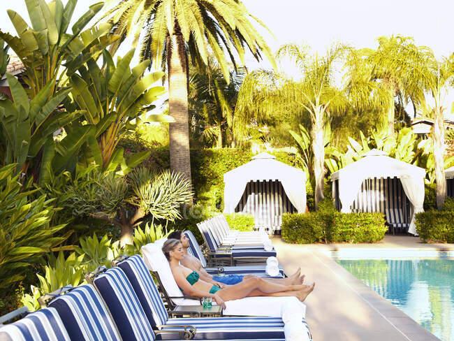 Coppia caucasica sdraiata in sdraio a bordo piscina — Foto stock