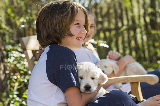 Niño de 6 años sosteniendo un cachorro inglés golden retriever - foto de stock