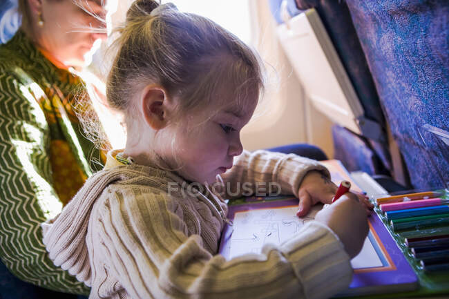 Young girl drawing on airplane, side view — Stock Photo