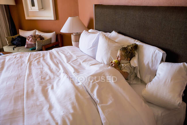 Young girl resting in hotel room bed — Stock Photo