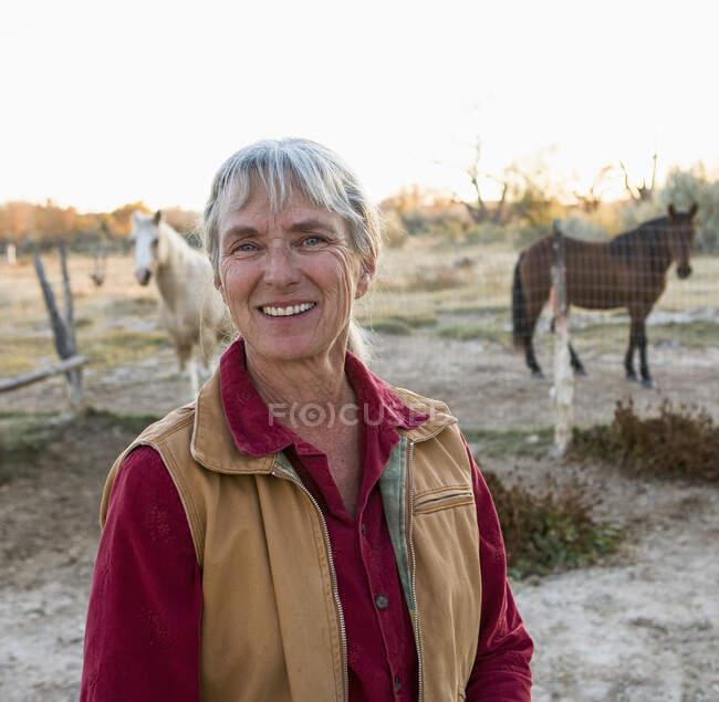 Donna matura a casa nella sua proprietà in un ambiente rurale, cavalli in un paddock — Foto stock