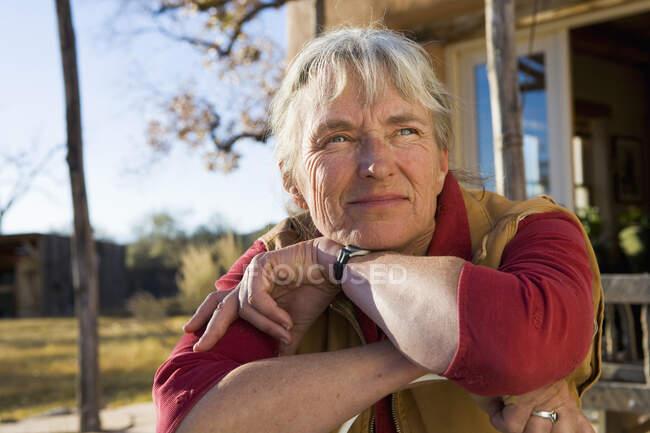 Зрелая женщина дома, на своей территории в сельской местности, кладет подбородок на руки — стоковое фото