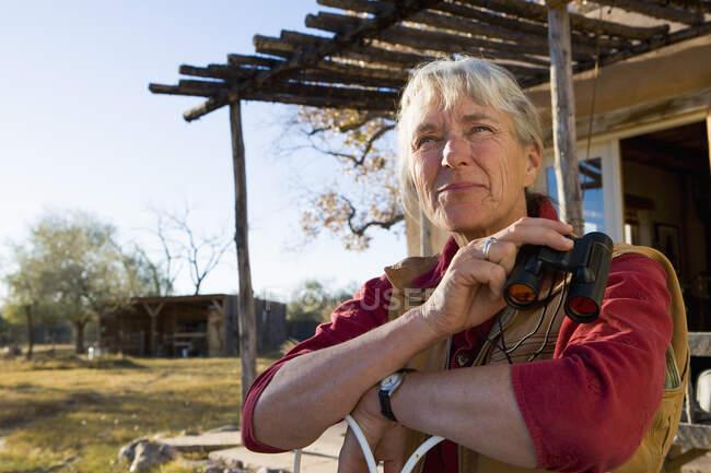 Donna matura a casa nella sua proprietà in un ambiente rurale con binocolo — Foto stock