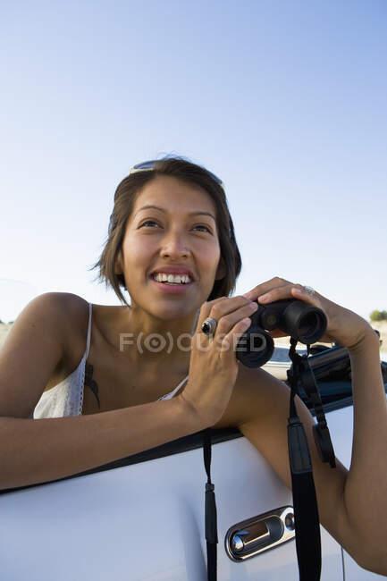 Indianerin im Sonnenkleid am Steuer eines weißen Cabrio-Sportwagens beim Blick durch ein Fernglas — Stockfoto