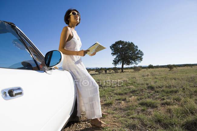 Indianerin im Sonnenkleid am Steuer eines weißen Cabrio-Sportwagens auf Feldweg in der Wüste mit einer Landkarte — Stockfoto