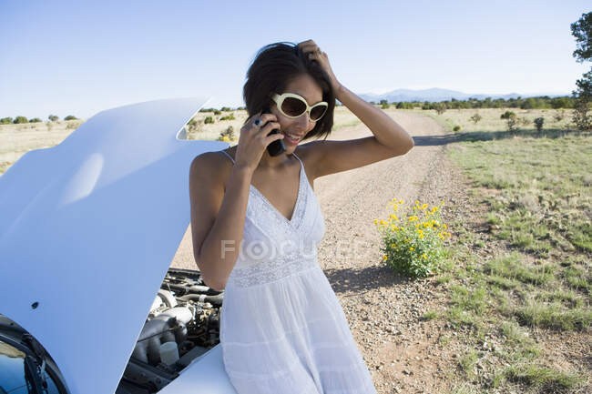 Indianerin im Sonnenkleid fährt weißen Cabrio-Sportwagen auf Feldweg in der Wüste und hat Probleme mit dem Auto — Stockfoto