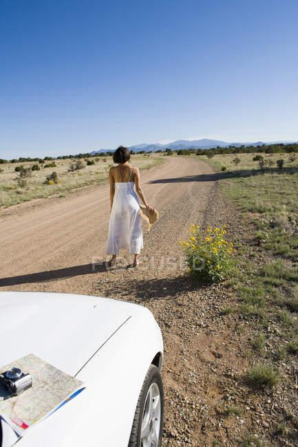 Indianerin im Sonnenkleid am Steuer eines weißen Cabrio-Sportwagens auf Wüstenschmutz — Stockfoto