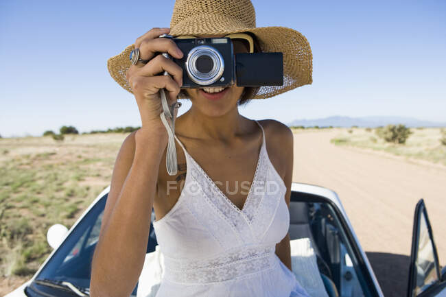 Indianerin im Sonnenkleid sitzt auf weißem Cabrio-Sportwagen und fotografiert — Stockfoto