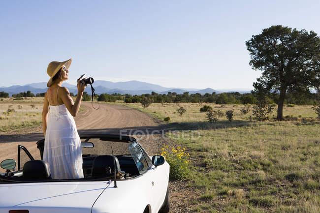 Indianerin im Sonnenkleid fährt weißen Cabrio-Sportwagen auf Feldweg in der Wüste — Stockfoto