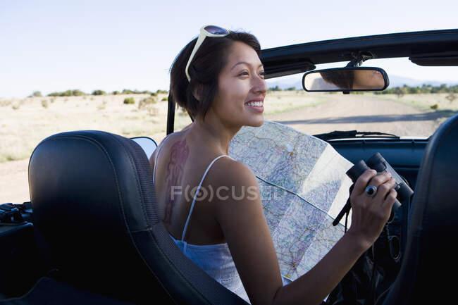 Indianerin im Sonnenkleid blickt auf eine Landkarte auf dem Beifahrersitz eines Cabrios — Stockfoto