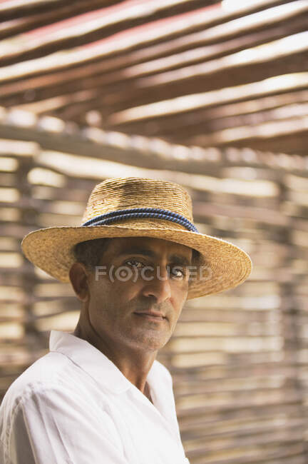 Portrait of man wearing straw hat and looking at camera — Stock Photo